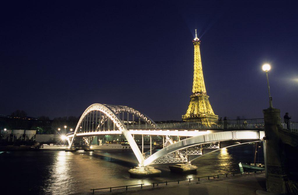 À noite, a Torre Eiffel e a passarela Debilly, que transpõe o Sena, se iluminam (Atout France/Jean François Tripelon-Jarry)