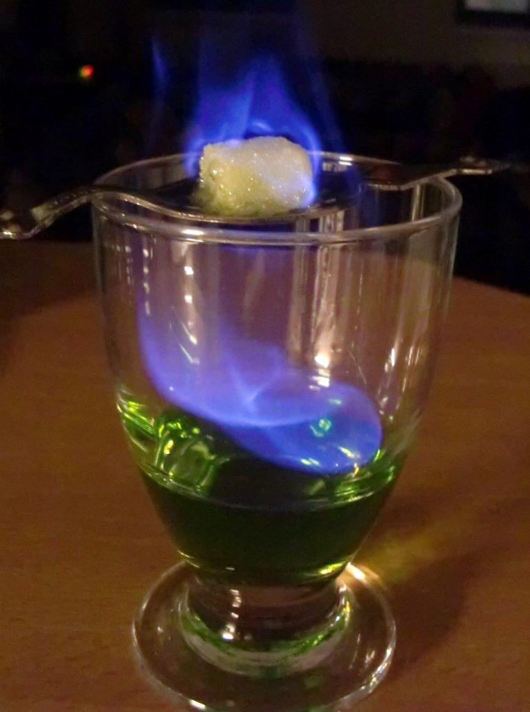 Tradicionalmente é preparada uma taça com uma colher furadinha sobre ela (também vendida nas absentheries), onde se coloca um torrão de açúcar. Em seguida o Absinto é despejado sobre o açúcar, ateando-se fogo até que ele derreta completamente, escorrendo da colher e se misturando com a bebida. Antes do consumo adiciona-se água gelada